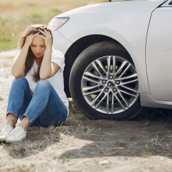 distraught woman sitting next to non functional vehicle